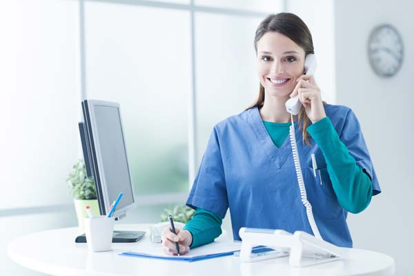 smiling woman answers phone in healthcare setting